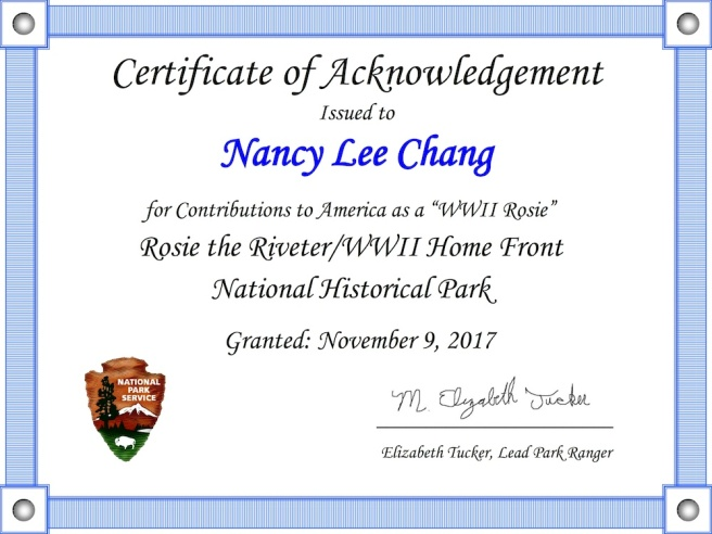 """Nancy Lee Chang receives a certificate of acknowledgement for her contributions as a """"WWII Rosie"""" from the Rosie the Riveter/WW II Home Front National Historic Park on November 9, 2017"""